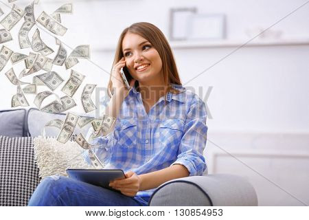 Financial concept. Make money on the Internet. Pretty woman talking on cell and holding tablet computer
