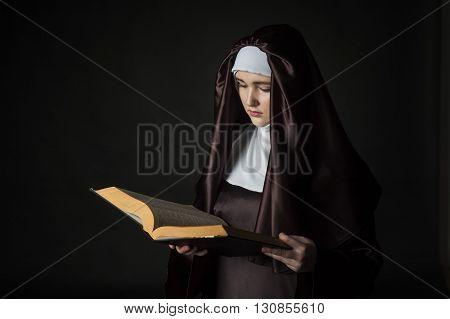 Young beautiful woman nun reading bible on black background. Low-key lighting.
