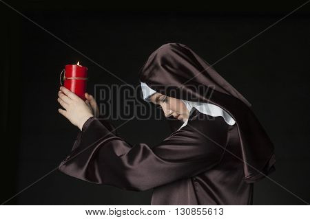 Young catholic nun is holding candle in her hands. Photo on black background. Side view.