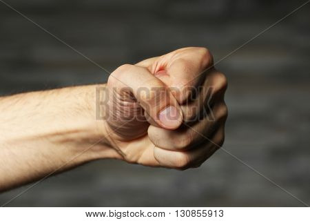 Male fist on grey background