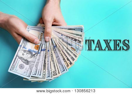 Male hands holding dollar banknotes against turquoise background.Taxes concept