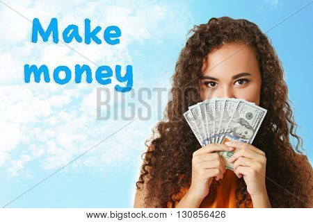 Beautiful young girl holding cash on blue sky background