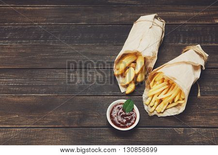 Potato wedges and french fries wrapped in brown wrapping paper. Fast food take away at rustic wood background. Choice of fried potatoes with tomato sauce. Chips, potato slices. Top view, copyspace