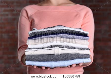 Woman hold clothes pile against brick wall background, close up