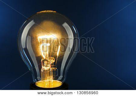 Illuminated light bulb on dark blue background