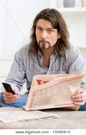 Man using mobile phone and holding newspaper in hand, sitting in living room at home.