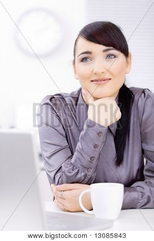 Young businessman sitting at desk at office, thinking, smiling.