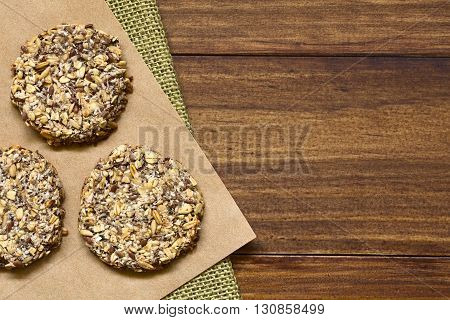 Vegan cookies made of banana oatmeal and roasted oat grains linseed poppy seeds grated coconut chia seeds and cinnamon powder photographed overhead with natural light