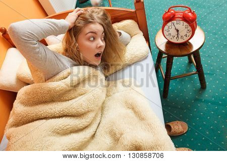 Panic woman waking up late in morning turning off alarm clock. Young girl laying in bed.