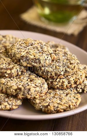 Vegan cookies made of banana oatmeal and roasted oat grains linseed poppy seeds grated coconut chia seeds and cinnamon powder served on plate with a cup of fresh herbal tea in the back photographed with natural light (Selective Focus Focus on the front of