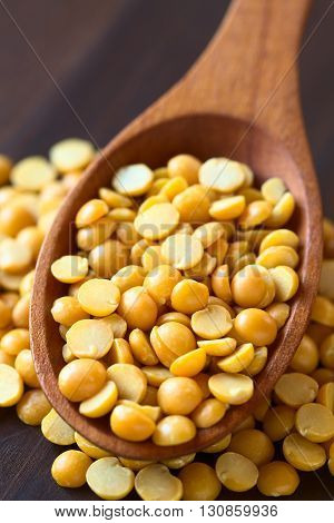 Raw yellow split peas in wooden spoon photographed on dark wood with natural light (Selective Focus Focus in the middle of the split peas in the spoon)