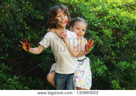 Children soiled with paint outdoor, having fun in the park. Little girl and boy hugging, faces and hands are colored. Children's creativity. Art for baby. Emotions. Children playing. Delight.
