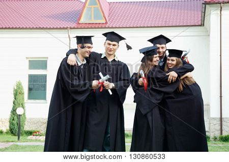 Students hold diplomas in their hands. They joyfully embrace. Young men dressed in black robes and caps.