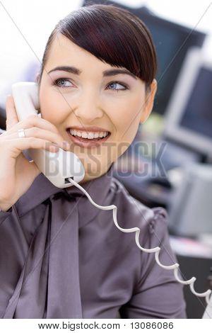 Operador de servicio cliente mujer joven feliz hablando por teléfono, sentado delante de la computadora