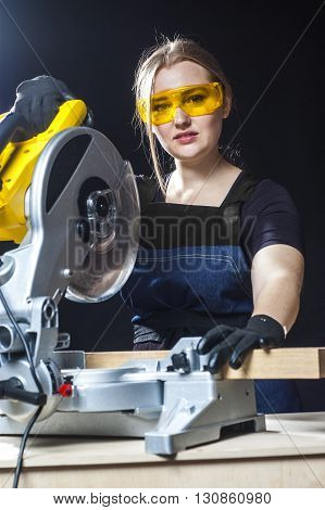 young beautiful woman in overalls and glasses with disk saw preparing for cutting. Photo on black background. close-up portrait.
