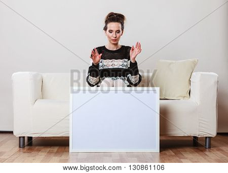 Advertisement concept. Fashionable woman sitting on sofa with blank presentation board. Female model showing banner sign billboard copy space for text.