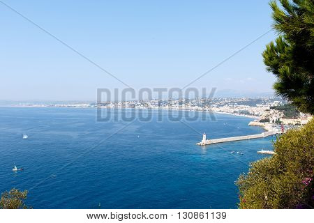 Wide angle view of blue water harbor of Nice, France, on the French Riviera, with lighthouse on quay