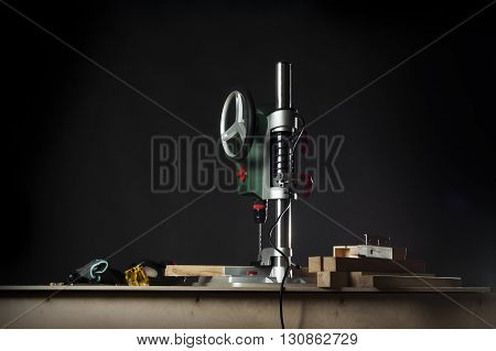 vertical drilling machine on table with tools. Photo on black background.