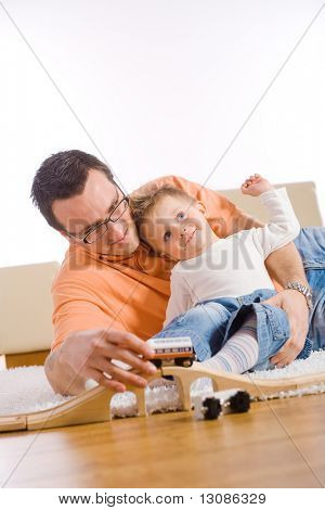 Little boy and father enjoying time together at home in living room.