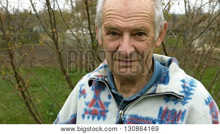Senior elderly aged old man portrait outdoors in the vegetable kitchen garden outside the house. Country rural scene.