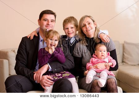 Portrait of happy family sitting on couch at home, smiling: father, mother, son, younger sister and a baby girl.