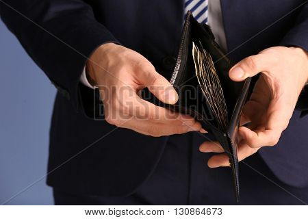 Man in a suit showing a purse with banknotes