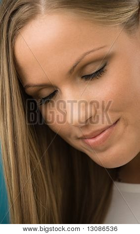 Closeup portrait of beautiful young woman, with long hair and eyes closed, daydreaming.