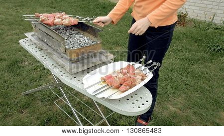 Girl puts barbecue bbq skewers with red meat on brazier with hot coals embers. Outdoors picnic concept.
