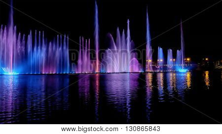 Amazing fantastic colorful fountain with bright illumination on the water pond or river with beautiful reflection at the evening or night. Beauty urban recreational concept.