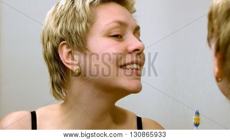 Pretty young woman brushing teeth in front of mirror. Everyday dental cleaning hygiene scene.