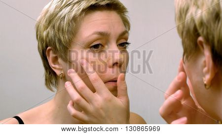 Beautiful young woman applies concealer foundation cream make up in front of mirror. Beauty and makeup concept.
