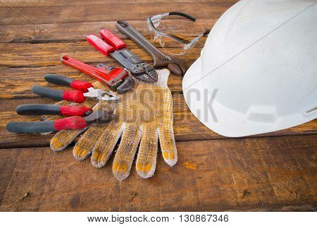 Construction tools on a wooden background with safety safety helmet