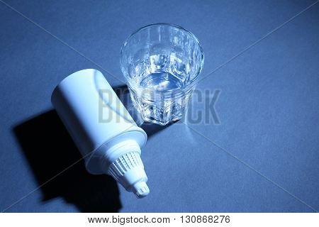 Filter cartridge and a glass of water on dark blue background
