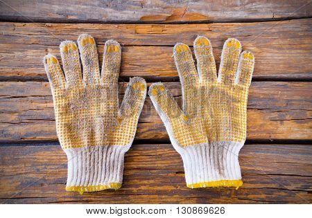 Cotton work gloves.Cotton knitted work gloves lying in the wood background.