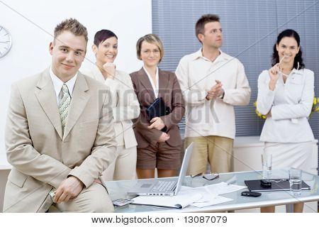 Young businessman sitting on office desk in front, looking at camera, smiling. Business team standing in the background.