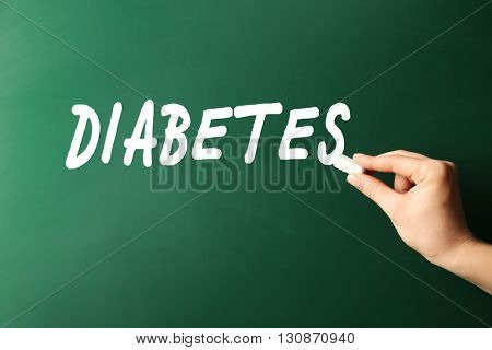 Female hand write Diabetes on blackboard