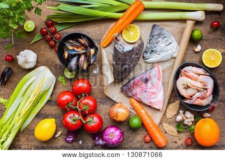 Fresh ingredients to cook fish soup bouillabaisse: fish heads onion lime lemon leak parsley tomato's carrot celery mussels shrimps. Top view