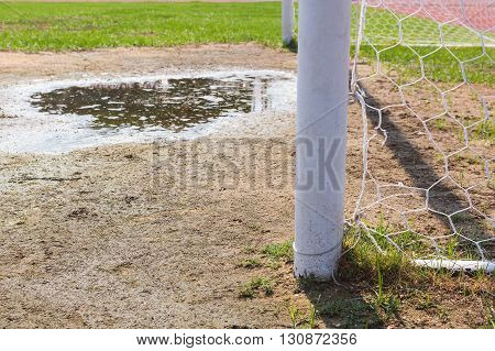 Soccer goal with green grass field background.