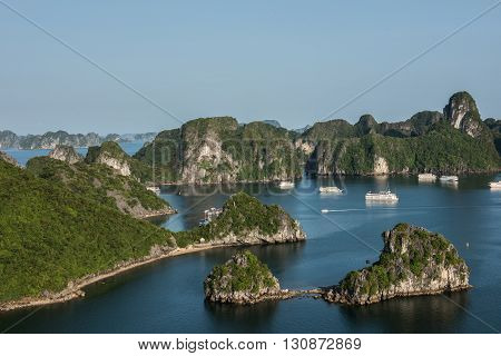View of the amazing limestone karsts in Ha Long Bay, Vietnam. Thousands of karst hills on the waters deliver an amazing view. Tourist boats are seen sailing on the water.