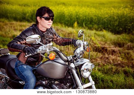 Woman biker in sunglasses and leather jacket racing on a motorcycle on the road.