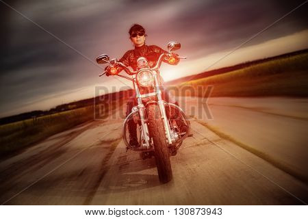 Woman biker in sunglasses and leather jacket racing on a motorcycle on the road. Filter applied in post-production.