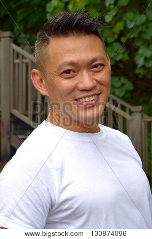 Mature Asian Man smiling happily posing outdoor