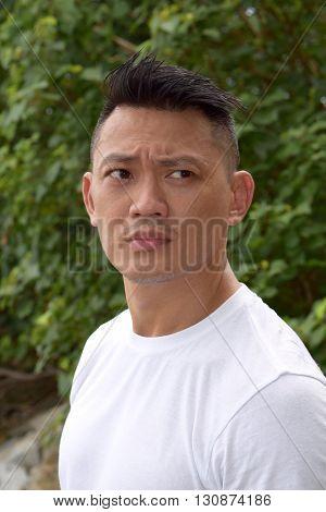 An asian mature man gazing afar at outdoor