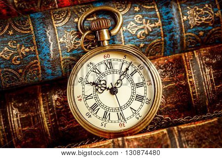 Vintage Antique pocket watch on the background of old books