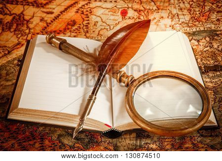Vintage still life - magnifying glass, old book and goose quill pen lying on an old map in 1565.