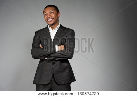 A happy attractive African American male wearing a custom suit posing in a studio setting on a gray background.