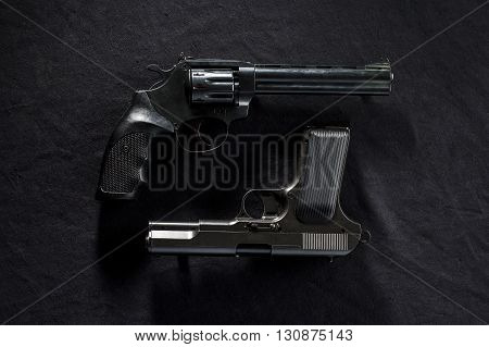 two old revolvers on black background. guns