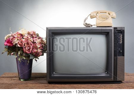 Vintage Television with old telephone on wood table on gray background