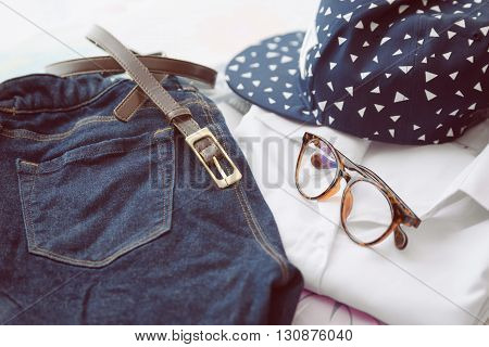 Woman's casual outfits background. White shirt, Blue jeans, Blue cap, brown belt and glass.
