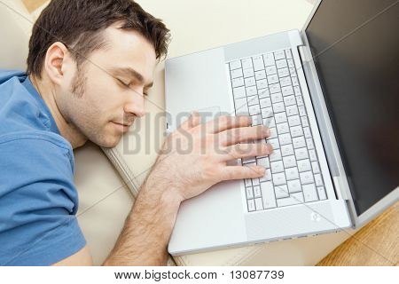 Man overslept by the keyboard of a laptop computer. eyes closed, high-angle view.
